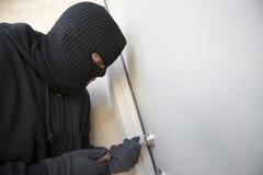 Einbrecher Working On Lock von Front Door lizenzfreies stockbild