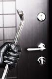 Einbrecherhandholdingbrechstangebruch-Öffnungstür Stockbild