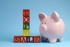 Eind van het bericht van de Begrotingsjaarverkoop op bouwstenen met spaarvarken Stock Foto's