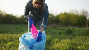 Einde plastic, sociaal concept Het meisje in jeans verzamelt afval in het park in een grote blauwe plastic zak stock footage