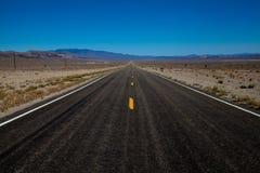 Eindeloze bestratingsstreep door de hete woestijn van Californië royalty-vrije stock fotografie