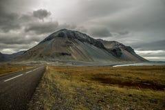 Eindeloze weg bij de kust met berg stock foto