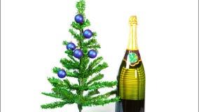 Eindemotie, nieuwe jaar` s ballen op een nieuwe jaarboom en een reusachtige fles mousserende wijn stock footage