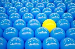 Eindeutige gelbe Kugel unter blauen Kugeln Stockbild