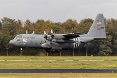 USAF C-130 Hercules plane invasion stripes. EINDHOVEN, THE NETHERLANDS - JUN 22, 2018: US Air Force Lockheed C-130H Hercules transport plane with D-Day invasion royalty free stock photos