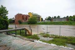 Eindrucksvoller Auspuff fließt in Flussregenwasser und -schlamm Lizenzfreie Stockfotografie