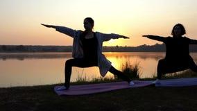 Eindrucksvoller Sonnenuntergang und Frauen, die Yoga-Übung des Kriegers-12 auf einer See-Bank tun stock video