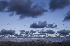 Eindrucksvoller Sonnenunterganghimmel mit dem Vollmond und den Schichten von Wolken, die sich unten in Richtung zum Horizont übe stockfotos