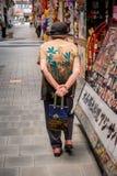 Eine ältere Frau in einem Hut und mit einer Tasche gehend hinunter die Straße stockbild