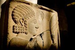 Eine Ägypten-Skulptur des menschlichen Gesichtes auf dem gealterten Ziegelstein Lizenzfreie Stockfotografie