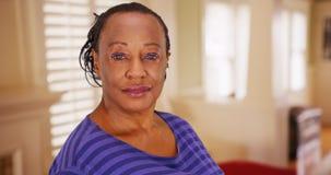 Eine ältere Afroamerikanerfrau wirft für ein Porträt in ihrem Haus auf Stockbild