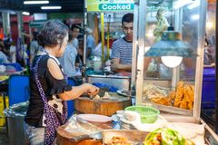 Eine ältere Frau bereitet sich chiken für Verkauf vor Lizenzfreies Stockfoto