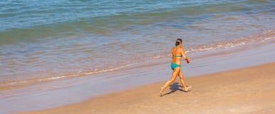 Eine ältere Frau, die allein auf einem Strand läuft Lizenzfreie Stockfotos