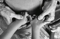 Eine ältere Frau, die Kind-` s Hände, einen hölzernen Stock auf der Straße hält Urgroßmutter und Großenkel Schwarzweiss--phot stockfotografie