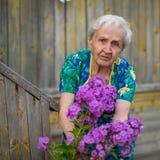 Eine ältere Frau, die sich draußen für Blumen interessiert liebhaberei lizenzfreies stockfoto