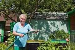 Eine ältere Frau im Garten mit Wasser Stockbilder