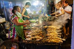 Eine ältere Frau kocht Fische Lizenzfreies Stockfoto