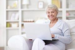 Eine ältere Frau mit einem Laptop stockfoto