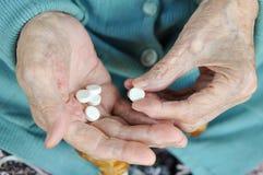 Eine ältere Frau mit einem Stock, der eine Pille auf der Straße hält 90 Jahre gesundheit Konzeptkrankheit und -gesundheitswesen stockfotografie