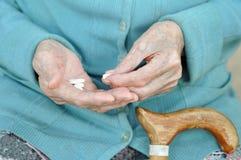Eine ältere Frau mit einem Stock, der eine Pille auf der Straße hält 90 Jahre gesundheit Konzeptkrankheit und -gesundheitswesen stockbilder