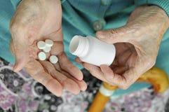 Eine ältere Frau mit einem Stock, der eine Pille und einen Behälter auf der Straße hält gesundheit Modell Abschluss oben lizenzfreies stockbild