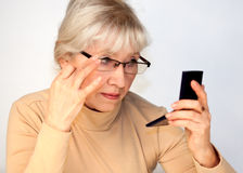 Eine ältere Frau schaut im Spiegel Stockbilder