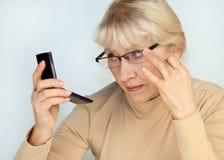 Eine ältere Frau schaut im Spiegel Stockfoto