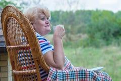 Eine ältere Frau sitzt in einem Weidenschaukelstuhl und in den Getränken ein Tasse Kaffee Entspannen Sie sich in einem Landhaus stockfotos