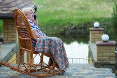 Eine ältere Frau sitzt in einem Weidenschaukelstuhl und in der Unterhaltung an einem Handy Gute Kommunikation Entspannen Sie sich lizenzfreies stockfoto