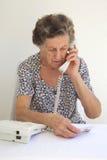 Eine ältere Frau spricht am Telefon Stockbild