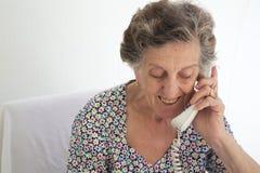 Eine ältere Frau spricht am Telefon Stockbilder
