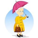 Eine ältere Frau unter einem Regenschirm Lizenzfreie Stockfotos