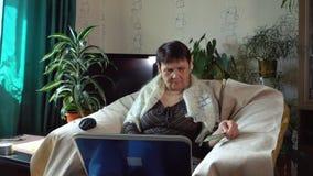 Eine ältere Frau zahlt für einen Kauf im Internet mit einer Kreditkarte stock footage