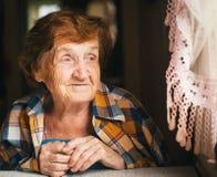 Eine ältere glückliche Frau schaut heraus das Fenster Lizenzfreie Stockfotografie