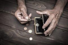 Eine ältere Person hält die Münzen über der alten leeren Geldbörse E Lizenzfreies Stockfoto