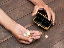 Eine ältere Person hält die Münzen über der alten leeren Geldbörse E Stockbild