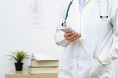 Eine Ärztin, die auf Smartphone simst stockbilder