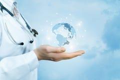 Eine Ärztin mit einem Stethoskop auf ihrem Hals hält eine Kristall-, funkelnde globale Karte auf ihrer Hand stockbilder