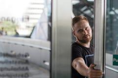 Eine öffnende Glastür des bärtigen Mannes stockfoto