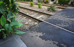 Eine Überfahrtweise auf Eisenbahnlinie mit Busch und Baum auf Seitenfoto eingelassenem Duri Tangerang stationieren Indonesien Lizenzfreie Stockbilder