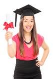 Eine überglückliche Frau, die ein Diplom hält Stockbild