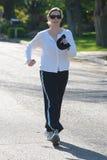 Eine überzeugte Frauenleistung geht hinunter eine Straße Lizenzfreies Stockfoto