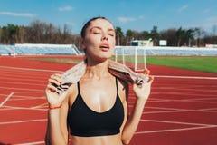 Eine überzeugte Mädchenfrau mit einem Tuch um seinen Hals nach einer harten Praxis schaut zu mehr bereit Stockbilder