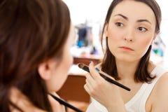 Eine Abbildung einer Spiegelreflexion eines schönen Mädchens, das sich ein setzt Lizenzfreie Stockbilder