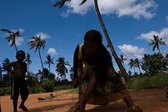 Eine afrikanische Dame, die eine Kokosnuss hält, um die Spitze zu schneiden Lizenzfreie Stockbilder
