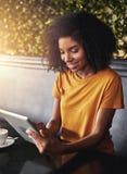 Eine afrikanische junge Frau unter Verwendung der digitalen Tablette im Café lizenzfreies stockfoto