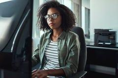 Eine afrikanische junge Geschäftsfrau, die an ihrem Schreibtisch arbeitet lizenzfreies stockbild