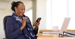 Eine Afroamerikanergeschäftsfrau benutzt ihren Handy an ihrem Schreibtisch lizenzfreie stockfotografie