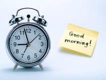 Eine Alarmuhr und eine gelbe Anmerkung Stockbild