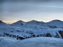 Eine alpine Szene des Winters Gebirgsunter einem blauen Himmel Lizenzfreie Stockfotografie